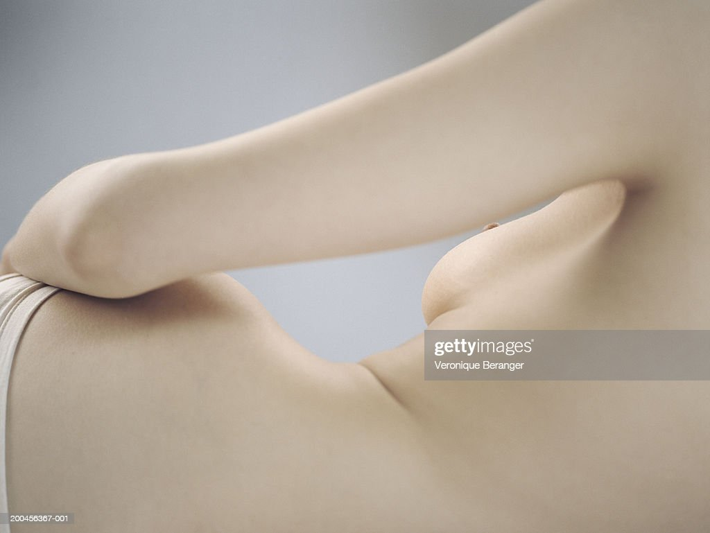 Semi-naked young woman reclining, rear view, mid section : Stock Photo