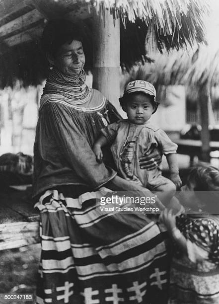 A Seminole Indian grandmother sits with her two grandchildren Florida early to mid 20th century The Seminole Indians are from the Muskhogean tribe of...