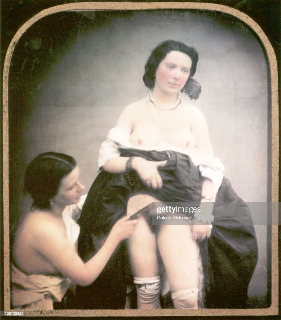 A semi-nude woman is combing the pubic hair of another woman standing next to her with her skirt lifted and her blouse pulled down. 1850. Hand-colored stereoscopic daguerreotype.