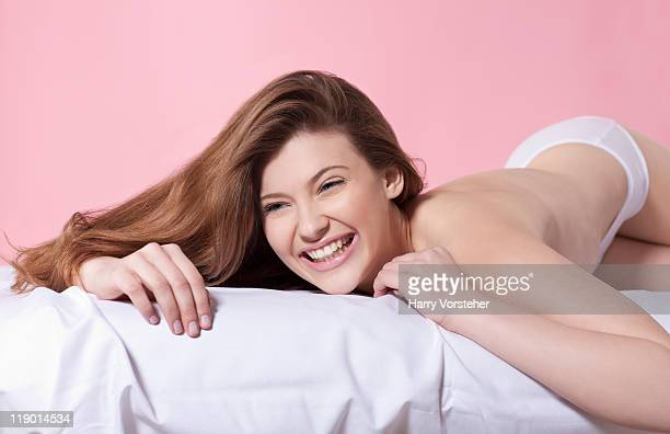 Semi-nude woman laying on bed
