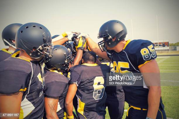 Semi-pro football team huddling to discuss play during game