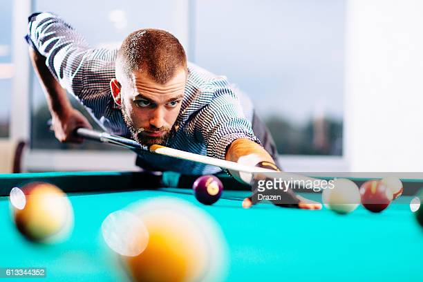Semi-professional pool game player ready for the shot