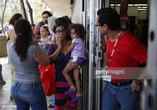 Semiramis Colon her child Keylianis Rodas wait in line to get into a grocery store as they deal with the aftermath of Hurricane Maria on September 26...