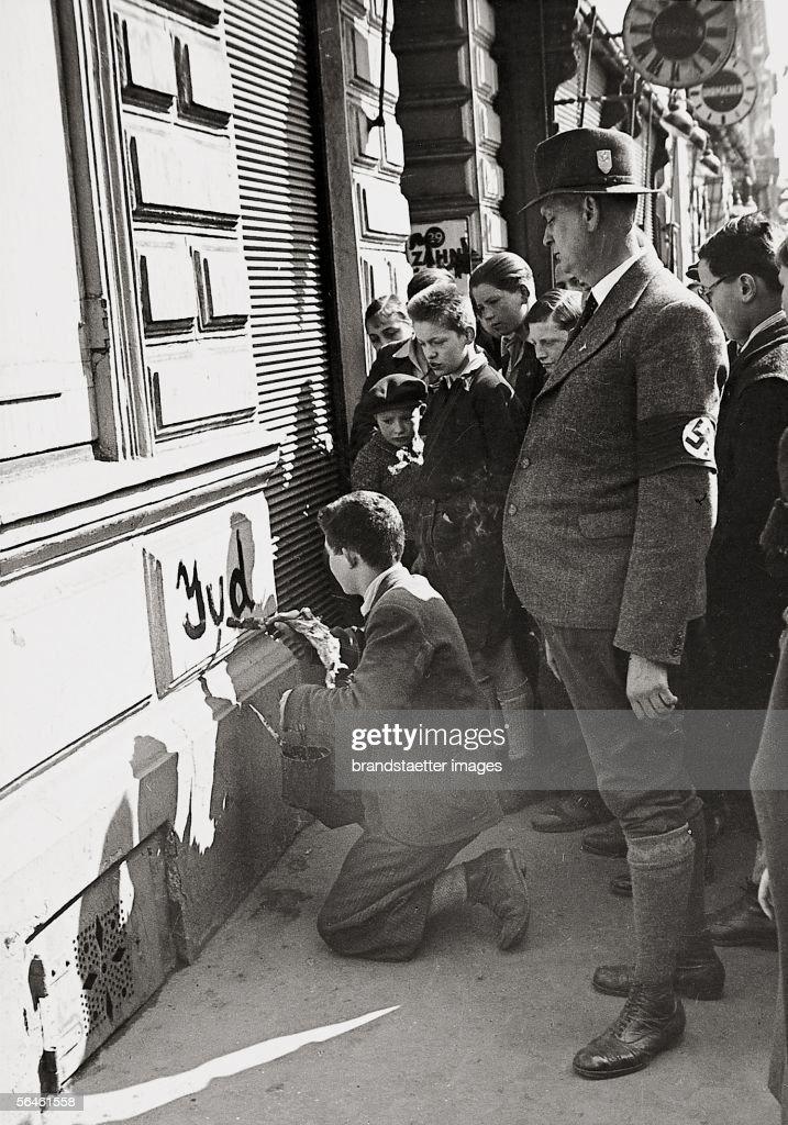 Semitic Excesses Vienna 1938 A boy marking a house with the inscription 'Jud' numerous bystanders [Antisemitische Ausschreitungen Wien 1938 Ein Bub...