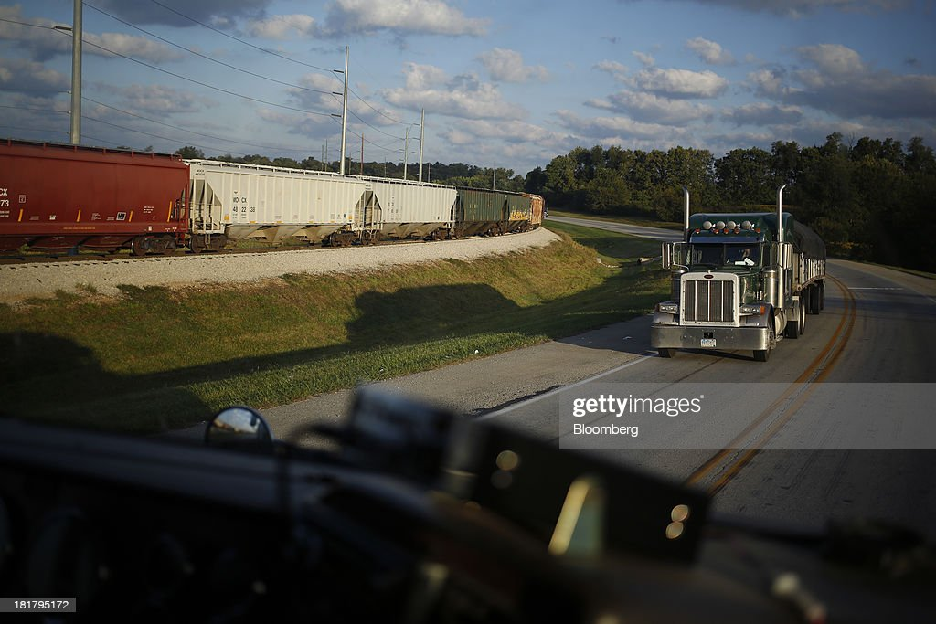 A semi-trailer truck destined for the Consolidated Grain & Barge Co. facility passes by grain railroad cars in Jeffersonville, Indiana, U.S., on Tuesday, Sept. 24, 2013. Private exporters reported to the U.S. Department of Agriculture (USDA) export sales of 197,200 metric tons of corn for delivery to Mexico during the 2013 and 2014 marketing year. Photographer: Luke Sharrett/Bloomberg via Getty Images