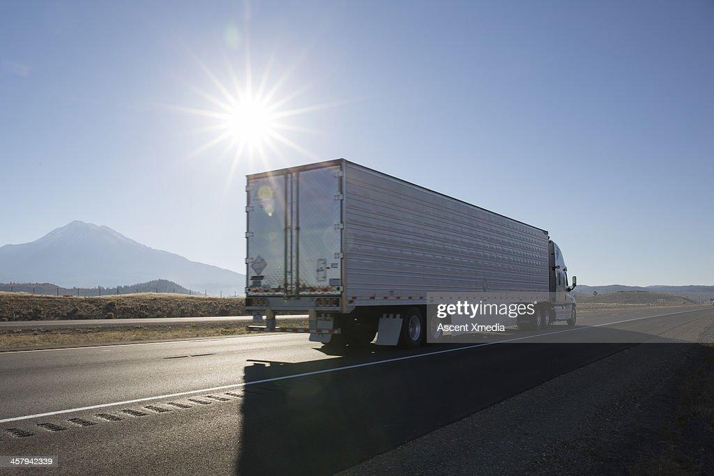 Semi-trailer truck motors along empty highway : Stock Photo