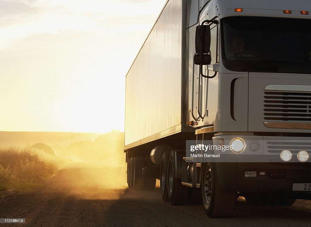 Semi-truck driving on dusty dirt road : Stock Photo