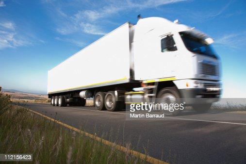 Semi-truck driving on remote road : Stock Photo