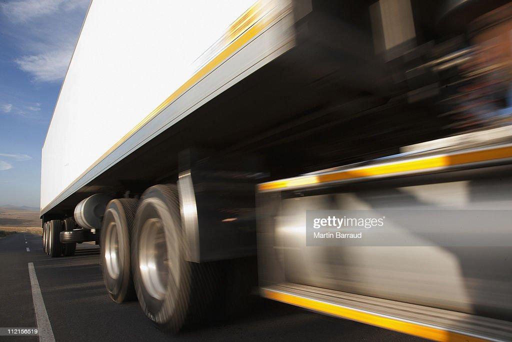 Semi-truck speeding on remote road : Stock Photo