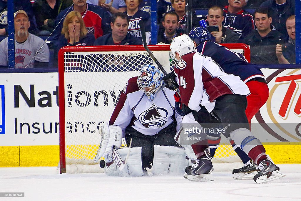 Semyon Varlamov #1 of the Colorado Avalanche makes a save as teammate Tyson Barrie #4 checks Blake Comeau #14 of the Columbus Blue Jackets as during the third period on April 1, 2014 at Nationwide Arena in Columbus, Ohio. Colorado defeated Columbus 3-2 in overtime.