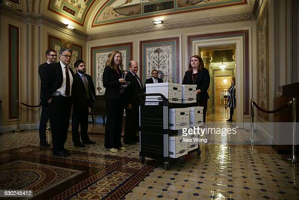 S Sen Al Franken and Sen Christopher Coons watch as boxes of questionnaire arrive prior to a press availability May 10 2016 on Capitol Hill in...