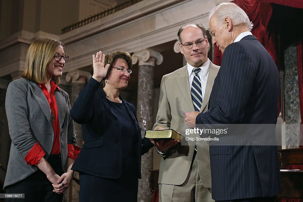 U.S. Sen. Amy Klobuchar (D-MN) 2nd L) participates in a reenacted swearing-in with her husband John Bessler, daughter Abigail Bessler and U.S. Vice President Joe Biden in the Old Senate Chamber at the U.S. Capitol January 3, 2013 in Washington, DC. Biden swore in the newly-elected and re-elected senators earlier in the day on the floor of the current Senate chamber.