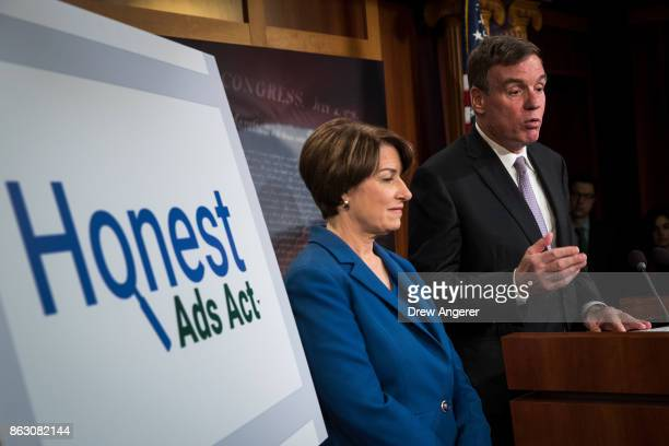 Sen Amy Klobuchar looks on as Sen Mark Warner speaks during a press conference to introduce the 'Honest Ads Act' on Capitol Hill October 19 2017 in...
