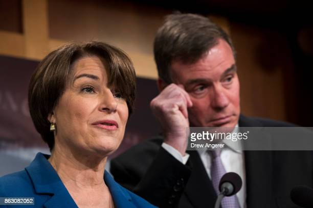Sen Amy Klobuchar speaks as Sen Mark Warner looks on during a press conference to introduce the 'Honest Ads Act' on Capitol Hill October 19 2017 in...