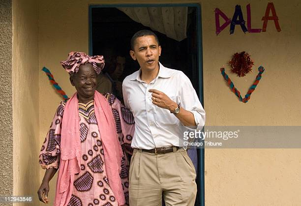 US Sen Barack Obama emerges with his grandmother Sarah Hussein Obama from her house in his family's village of Kogelo Kenya on August 26 2006