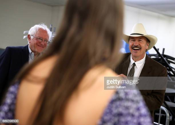 S Sen Bernie Sanders and democratic US Congressional candidate Rob Quist laugh as they talk with Halladay Quist before the start of a campaign rally...