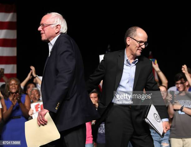 Sen Bernie Sanders and DNC Chair Tom Perez walk past each other as Sen Sanders takes to the stage to speak during their 'Come Together and Fight...