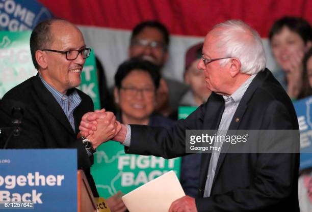 Sen Bernie Sanders greets DNC Chairman Tom Perez on stage as he gets ready to speak to a crowd of supporters at a Democratic unity rally at the Rail...