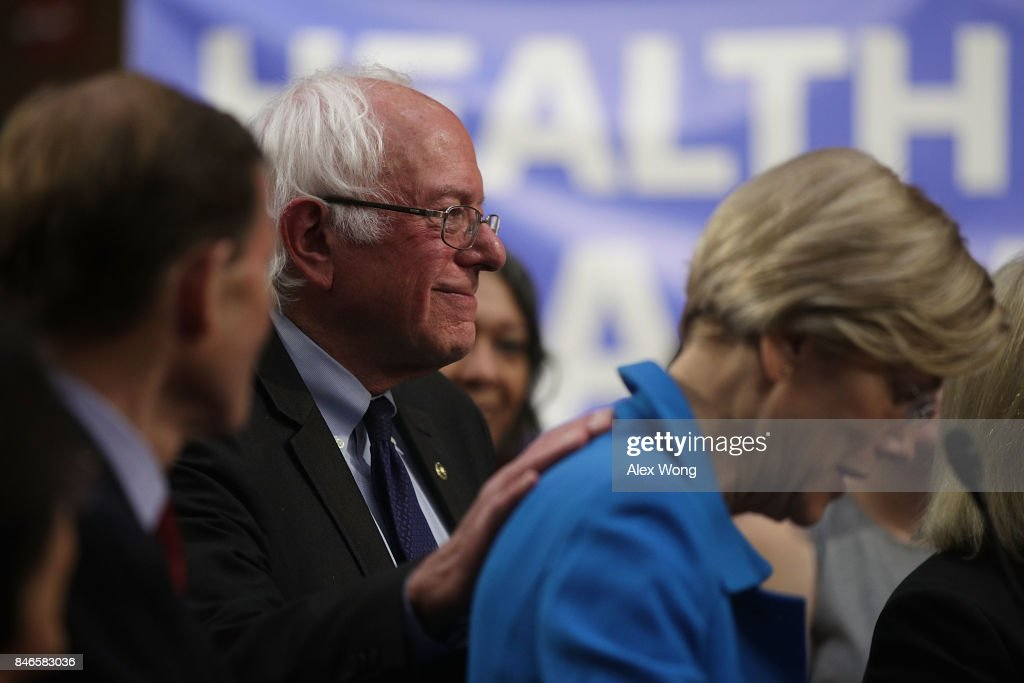 U.S. Sen. Bernie Sanders (I-VT) (2nd L) pats on the back of Sen. Elizabeth Warren (D-MA) (R) during an event on health care September 13, 2017 on Capitol Hill in Washington, DC. Sen. Sanders held an event to introduce the Medicare for All Act of 2017.