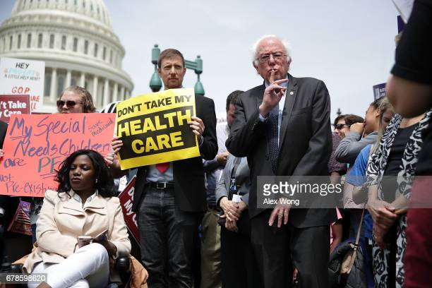 S Sen Bernie Sanders signals the crowd to quiet down for a speaker during a Stop 'Trumpcare' rally May 4 2017 in front of the Capitol in Washington...