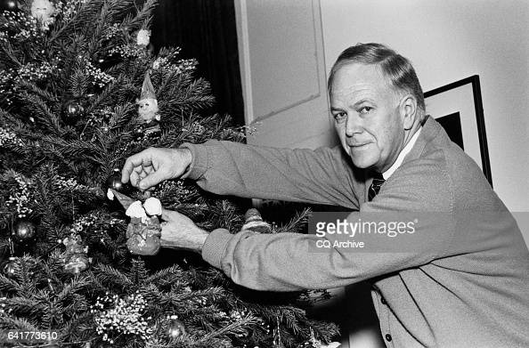 Sen Bob Packwood ROre proudly places a Santa arrangement on one of the Christmas tree at his office as part of a decoration contest December 18 1989