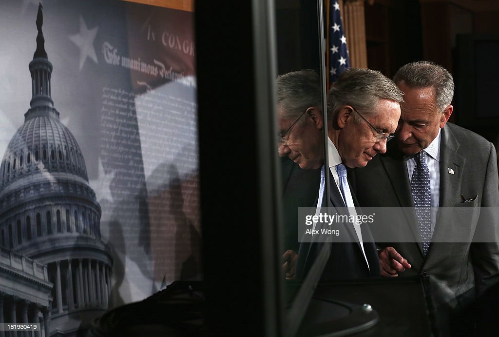U.S. Sen. <a gi-track='captionPersonalityLinkClicked' href=/galleries/search?phrase=Charles+Schumer&family=editorial&specificpeople=171249 ng-click='$event.stopPropagation()'>Charles Schumer</a> (D-NY) (R) talks to Senate Majority Leader Sen. <a gi-track='captionPersonalityLinkClicked' href=/galleries/search?phrase=Harry+Reid+-+Politician&family=editorial&specificpeople=203136 ng-click='$event.stopPropagation()'>Harry Reid</a> (D-NV) (L) during a news conference September 26, 2013 on Capitol Hill in Washington, DC. The Democratic senators held a news conference to call on the House Republicans not to shutdown the government.