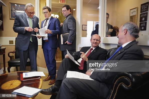 Sen Charles Schumer talks with staff members as he and Sen Chris Coons and Sen Robert Casey prepare for a news conference following meetings between...
