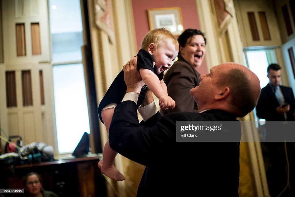 Sen. Chris Coons (D-DE) plays with 7 month old Max Huijbregts of Washington before the start of the Senate Democrats' news conference in the Capitol on Wednesday, May 25, 2016, to demand that the full Congress immediately pass emergency funding to combat the spread of the Zika virus in the United States.