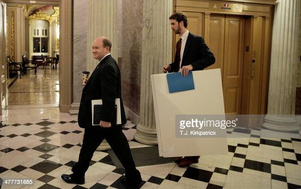 S Sen Chris Coons walks with a staff member on his way to join Senate Democrats speaking nonstop on the chamber floor about climate change on March...