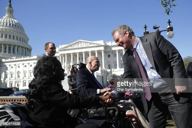 Sen Chris Van Hollen greets Kent Keyser before a news conference with people who may be negatively affected by the proposed American Health Care Act...