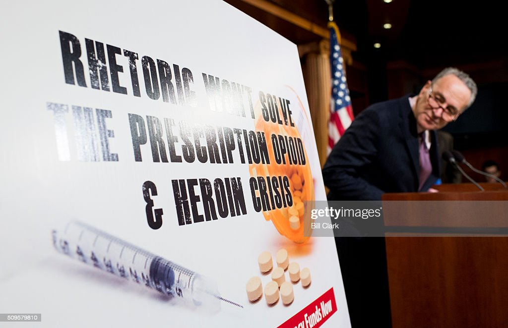 Sen. Chuck Schumer, D-N.Y., looks at the poster during the Senate Democrats' news conference to 'demand emergency funding to tackle prescription opioid and heroin crisis' on Thursday, Feb. 11, 2016.