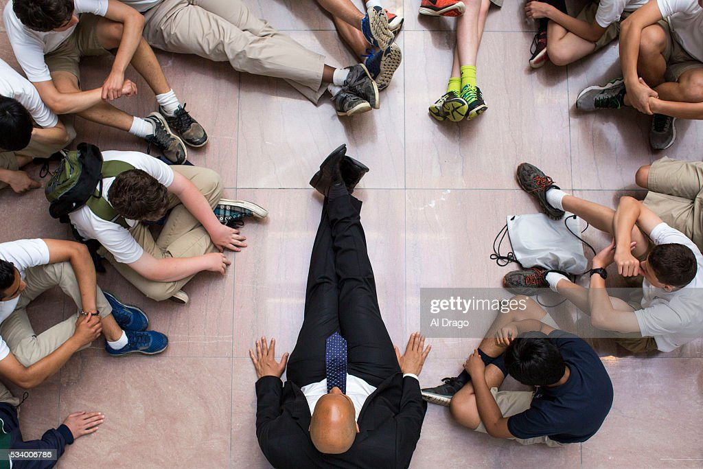 STATES - MAY 24 - Sen. Cory Booker, D-N.J., sits on the floor as he meets with 8th graders from Princeton Academy of the Sacred Heart on their end of year trip to Washington, in the atrium of the Hart Senate Office Building, in Washington, Tuesday, May 24, 2016. In an unofficial right of passage, thousands of middle school students visit the nation's capital each year after after studying the United States history in school.