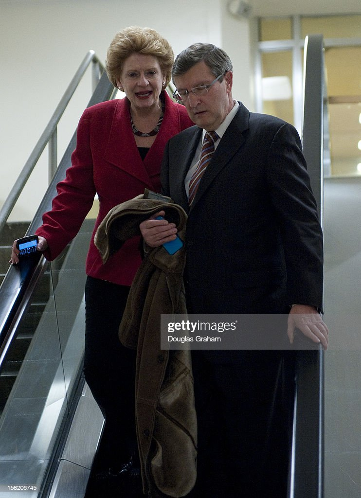 Sen. Debbie Stabenow, D-MI., and Kent Conrad, D-ND., walk through the Senate subway on their way to the Senate Office Buildings on December 11, 2012.