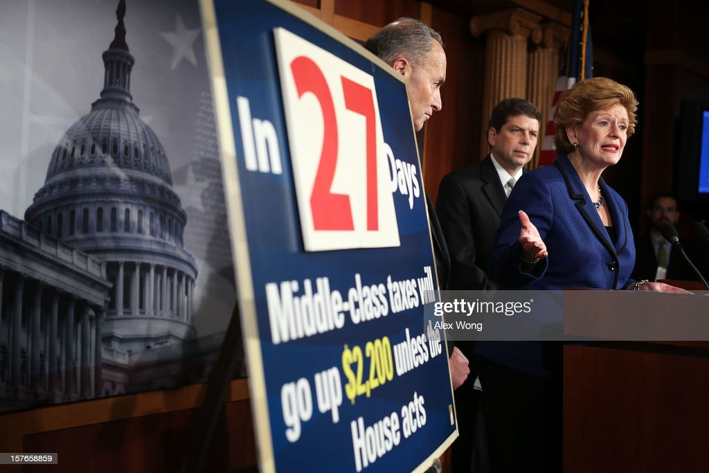 U.S. Sen. <a gi-track='captionPersonalityLinkClicked' href=/galleries/search?phrase=Debbie+Stabenow&family=editorial&specificpeople=221624 ng-click='$event.stopPropagation()'>Debbie Stabenow</a> (D-MI) (R) speaks as Sen. <a gi-track='captionPersonalityLinkClicked' href=/galleries/search?phrase=Charles+Schumer&family=editorial&specificpeople=171249 ng-click='$event.stopPropagation()'>Charles Schumer</a> (D-NY) (L) and Sen. <a gi-track='captionPersonalityLinkClicked' href=/galleries/search?phrase=Mark+Begich&family=editorial&specificpeople=5592439 ng-click='$event.stopPropagation()'>Mark Begich</a> (D-AK) listen during a news conference December 5, 2012 on Capitol Hill in Washington, DC. The senators held a news conference to call on House Republicans to pass the Senate-passed tax cut bill.