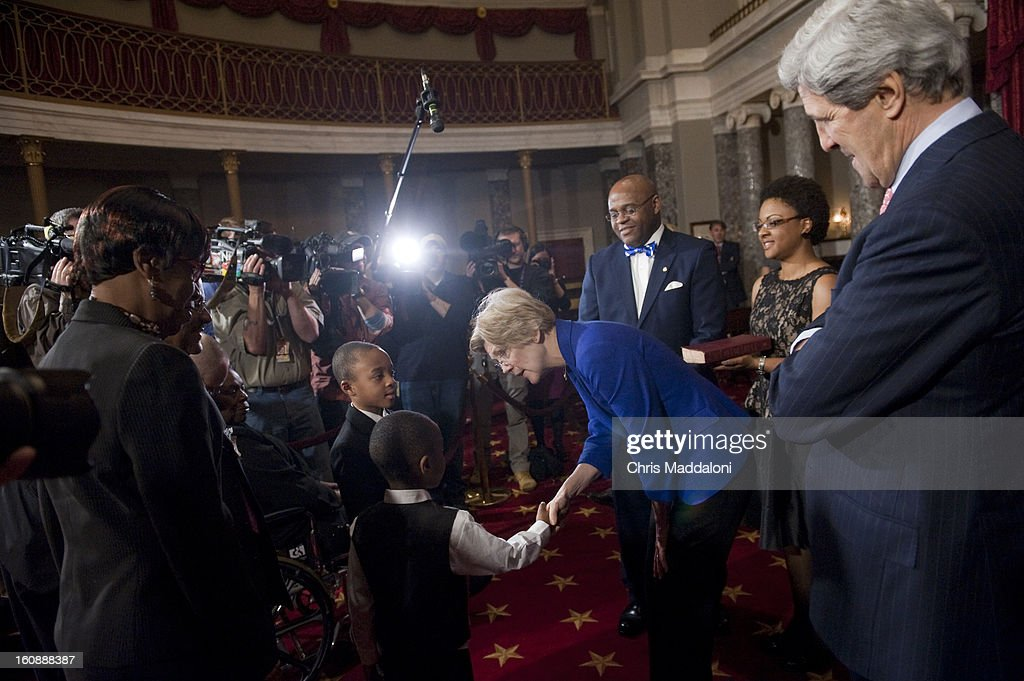 Sen. Elizabeth Warren, D-Mass., greets Sen.-designate William Cowan's children, Miles and Grant, as Secretary of State John Kerry watches before the mock swearing-in ceremony. Cowan is taking the place of Kerry in the Senate.