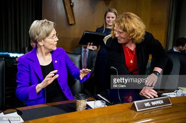 Sen Elizabeth Warren DMass left and Sen Heidi Heitkamp DN Dak talk before the start of the Senate Banking Housing and Urban Affairs Committee hearing...