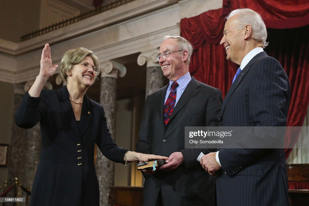 U.S. Sen. <a gi-track='captionPersonalityLinkClicked' href=/galleries/search?phrase=Elizabeth+Warren&family=editorial&specificpeople=5396017 ng-click='$event.stopPropagation()'>Elizabeth Warren</a> (D-MA) (L) participates in a reenacted swearing-in with her husband Bruce Mann and U.S. Vice President Joe Biden in the Old Senate Chamber at the U.S. Capitol January 3, 2013 in Washington, DC. Biden swore in the newly-elected and re-elected senators earlier in the day on the floor of the current Senate chamber.