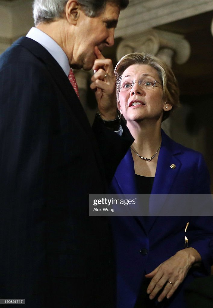 U.S. Sen. Elizabeth Warren (D-MA) (R) talks to Secretary of State and former U.S. Sen. John Kerry (D-MA) (L) during a re-enactment of the swearing-in for U.S. Senator William 'Mo' Cowan (D-MA) February 7, 2013 at the Old Senate Chamber of the U.S. Capitol in Washington, DC. Cowan was appointed by Massachusetts Governor Deval Patrick as interim U.S. Senator to fill the seat that left vacant by Secretary of State and former U.S. Sen. John Kerry.