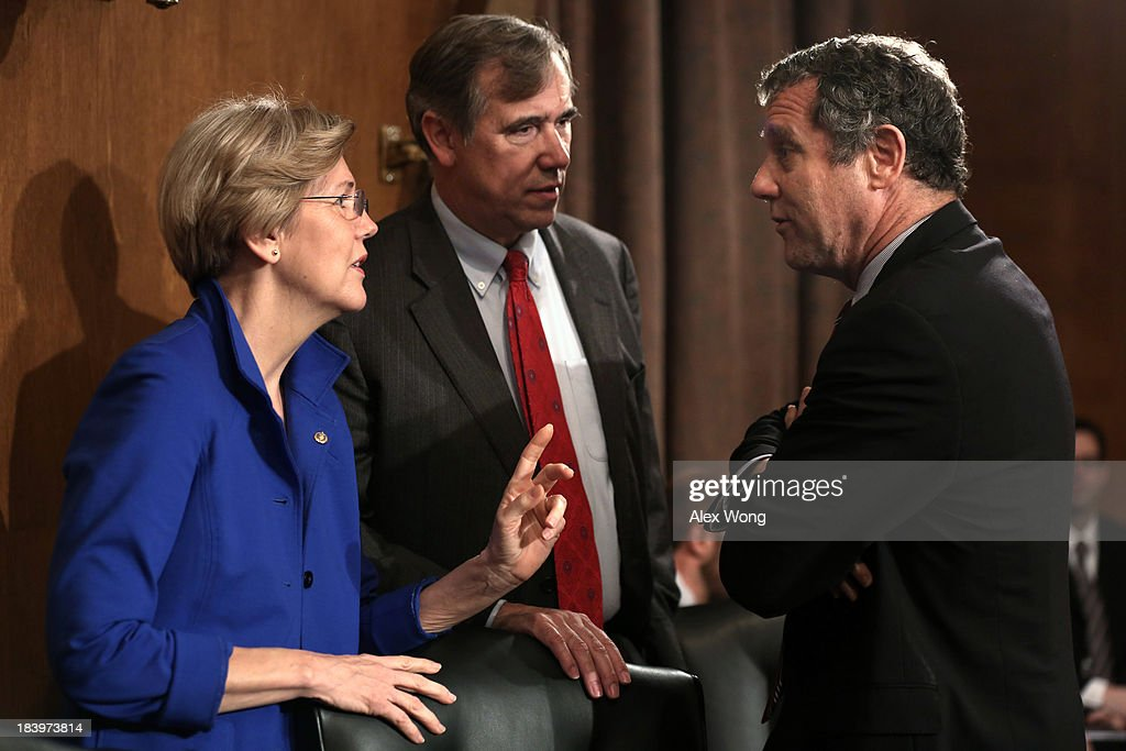 U.S. Sen. <a gi-track='captionPersonalityLinkClicked' href=/galleries/search?phrase=Elizabeth+Warren&family=editorial&specificpeople=5396017 ng-click='$event.stopPropagation()'>Elizabeth Warren</a> (D-MA) talks to Sen. <a gi-track='captionPersonalityLinkClicked' href=/galleries/search?phrase=Jeff+Merkley&family=editorial&specificpeople=5507302 ng-click='$event.stopPropagation()'>Jeff Merkley</a> (D-OR) and Sen. <a gi-track='captionPersonalityLinkClicked' href=/galleries/search?phrase=Sherrod+Brown&family=editorial&specificpeople=3986311 ng-click='$event.stopPropagation()'>Sherrod Brown</a> (D-OH) prior to a hearing before the Senate Banking, Housing and Urban Affairs Committee October 10, 2013 on Capitol Hill in Washington, DC. The committee held a hearing on 'Impact of a Default on Financial Stability and Economic Growth.'