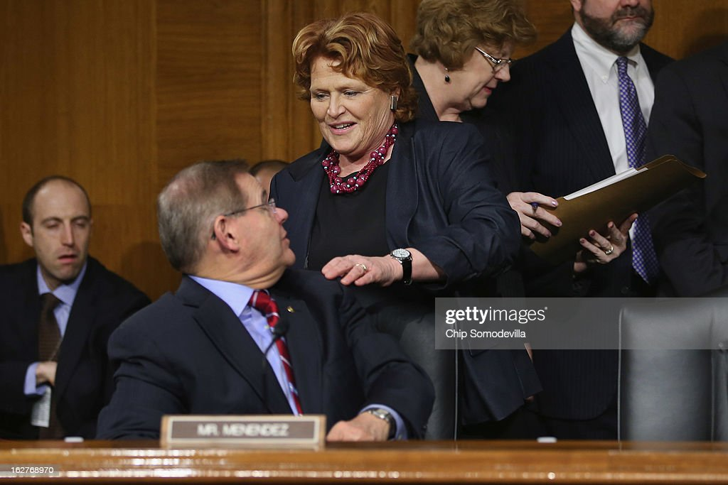 Sen. Heidi Heitkamp (D-ND) (C) greets Sen. <a gi-track='captionPersonalityLinkClicked' href=/galleries/search?phrase=Robert+Menendez&family=editorial&specificpeople=504931 ng-click='$event.stopPropagation()'>Robert Menendez</a> (D-NJ) before a hearing of the Senate Banking, Housing and Urban Affairs Committee after the release of The Semiannual Monetary Policy Report to the Congress February 26, 2013 in Washington, DC. Federal Reserve Bank Chairman Ben Bernanke urged Congress to avoid the harsh sequestration cuts scheduled to begin March 1 with a plan to reduce federal deficits more gradually. He warned the sequestration could harm the economic recovery.
