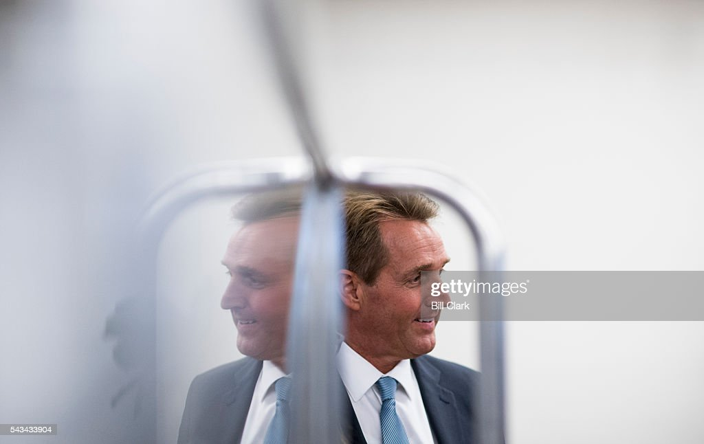 Sen. Jeff Flake (R-AZ) is reflected in one of the Russell Senate subway car windows as he speaks with a reporter as he leaves the Senate Republicans' policy luncheon on Tuesday, June 28, 2016.