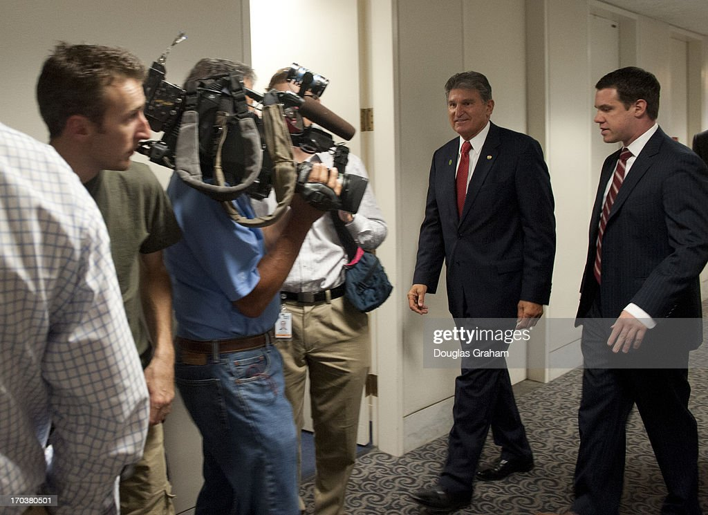 Sen. Joe Manchin, D-WVA., arrives at his office as TV crews clog the hallway outside as they wait to cover a press conference in his office with the Newtown families of the Sandy Hook shooting victims in the Hart Senate Office Building on June 12, 2013.