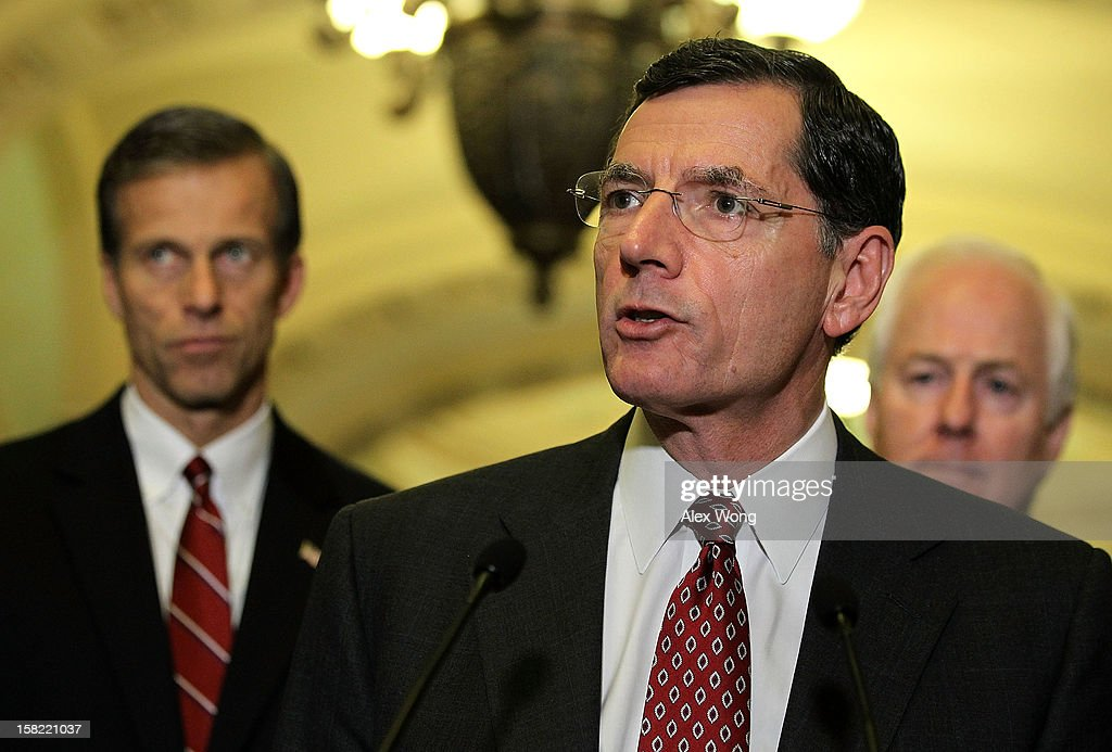 U.S. Sen. John Barrasso (R-WY) (C) speaks as Sen. <a gi-track='captionPersonalityLinkClicked' href=/galleries/search?phrase=John+Thune&family=editorial&specificpeople=534356 ng-click='$event.stopPropagation()'>John Thune</a> (R-SC) (L) and Sen. <a gi-track='captionPersonalityLinkClicked' href=/galleries/search?phrase=John+Cornyn&family=editorial&specificpeople=154884 ng-click='$event.stopPropagation()'>John Cornyn</a> (R-TX) (R) listen during a news briefing after the weekly Senate Republican Policy Luncheon December 11, 2012 on Capitol Hill in Washington, DC. McConnell discussed various topics with the media including the fiscal cliff issue saying 'time is running out.'