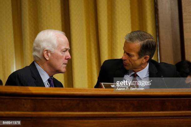 Sen John Cornyn speaks with Sen John Thune during a tax reform hearing before the Senate Finance Committee on Capitol Hill September 14 2017 in...