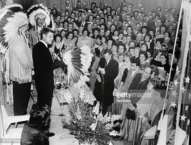 Sen John Kennedy admires Indian headdress presented to him by Alvin Blackdeer left chief counselor of Winnebago Indian Nation at a reception An...