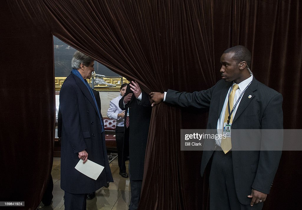 Sen. John Kerry, D-Mass., left, leaves the temporary coat check room set up in the rotunda for the 2013 Inaugural Luncheon following President Obama's inauguration on Monday, Jan. 21, 2013. The coat check staff could not locate his wife's coat.