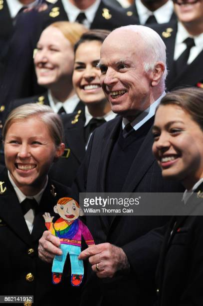 Sen John McCain poses for photos with a group of Naval cadets after receiving the 2017 Liberty Medal from former Vice President Joe Biden at the...