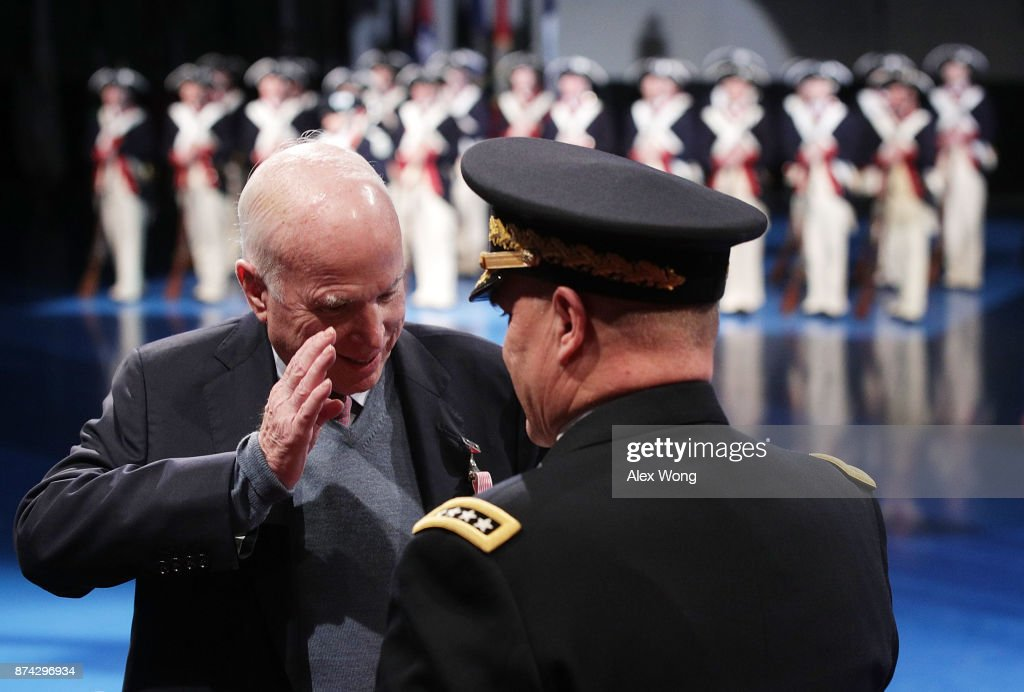 U.S. Sen. John McCain (R-AZ) (L) salutes to Army Chief of Staff Gen. Mark A. Milley (R) after he was presented with the Outstanding Civilian Service Medal during a special Twilight Tattoo performance November 14, 2017 at Fort Myer in Arlington, Virginia. McCain was honored for over 63 years of dedicated service to the nation and the U.S. Navy.