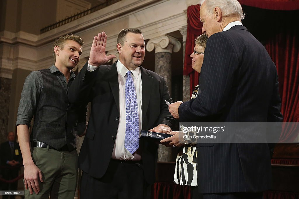 U.S. Sen. John Tester (D-MT) (2nd L) participates in a reenacted swearing-in with his wife Sharla Tester, son Shon Tester and U.S. Vice President Joe Biden in the Old Senate Chamber at the U.S. Capitol January 3, 2013 in Washington, DC. Biden swore in the newly-elected and re-elected senators earlier in the day on the floor of the current Senate chamber.
