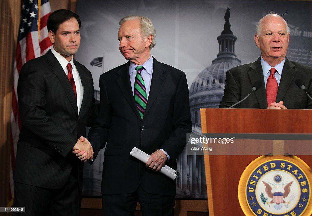 U.S. Sen. <a gi-track='captionPersonalityLinkClicked' href=/galleries/search?phrase=Joseph+Lieberman&family=editorial&specificpeople=236098 ng-click='$event.stopPropagation()'>Joseph Lieberman</a> (ID-CT) (C) shakes hands with Sen. <a gi-track='captionPersonalityLinkClicked' href=/galleries/search?phrase=Marco+Rubio+-+Politician&family=editorial&specificpeople=11395287 ng-click='$event.stopPropagation()'>Marco Rubio</a> (R-FL) (L) as Sen. Benjamin Cardin (D-MD) (R) speaks during a news conference about the crisis in Syria May 11, 2011 on Capitol Hill in Washington, DC. Lieberman and Rubio will introduce a resolution to calling on the U.S. government to have a tougher stance in the crisis in Syria.